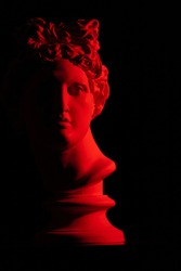 White plaster statue of a bust of Apollo Belvedere in red light on a black background