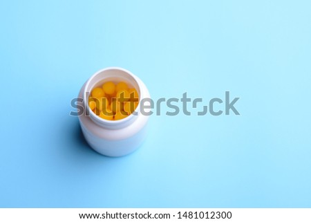 White plastic bottle with yellow ball pills inside. Bottle with prescribed pills stands on the blue table #1481012300