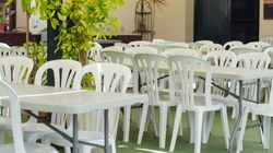 White plastic chairs around tables. ready for a large crowd of people for mass events and parties. The chairs are placed outside under the roof. Andalucia spain, forest park.