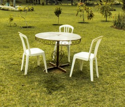 white plastic chairs on a metal table in a garden