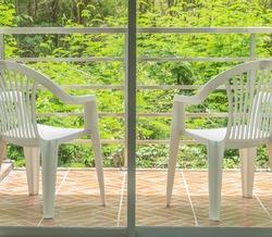white plastic chairs on balcony of hotel room inside garden