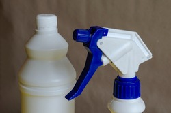 White plastic containers for household detergents on light brown background. White bottle with cork and spray bottle close-up. Trade or cleaning company.