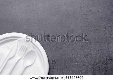 White plastic disposable tableware on gray background #615946604