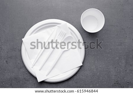 White plastic disposable tableware on gray background #615946844