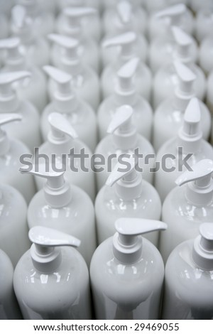 White plastic soap bottles in rows, cosmetics laboratory assembly line