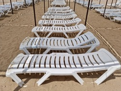 White plastic sun loungers arranged in a row on the sandy beach of the sea. Sun lounger rental is open.
