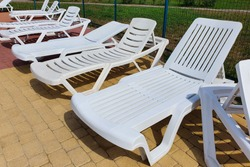 White plastic sun loungers in front of pool. No people, front view