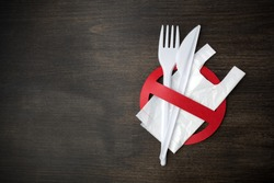 White plastic tableware on a wooden background as a symbol of environmental pollution. Ban single use plastic.