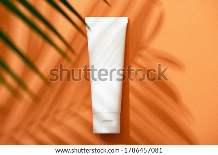 White plastic tube with face, hand and body cream on an orange background with palm leaves and shadow. Sun protection lotion, sunscreen. Summer skin care concept with spf flat lay. Mockup Stock foto ©