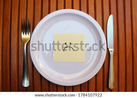 White plate and cutlery with a sad face drawing being served.  Stock photo ©