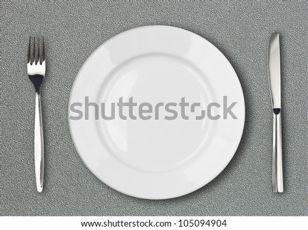White plate, fork and knife top view on gray plastic textured table surface