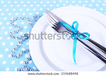 White plate, fork, knife and Christmas decoration on polka dot tablecloth closeup