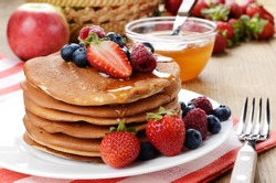 White plate full of pancakes with strawberries raspberries blueberries and honey