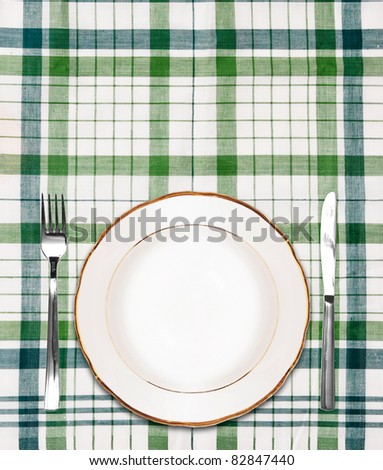 white plate on green checkered tablecloth with knife and fork
