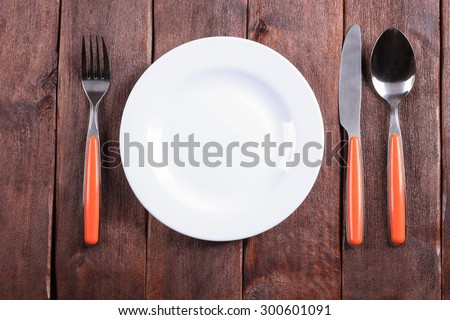 White plate on the table. Empty plate. Fork, knife and spoon on the table. Laying the table. Starvation diet. Template, background, space for text. Restaurant, catering, cafeteria. For food.