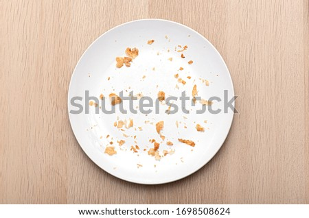 White Plate with Crumbs, dish with bread crumbs, top view