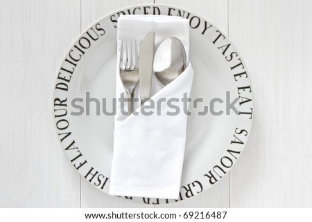 White plate with decorative words and silverware and serviette - stock photo