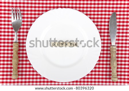 White plate with Dinner-lettering and cutlery