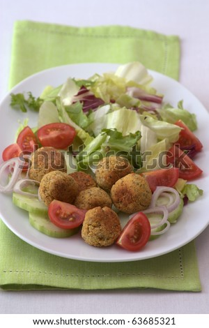 White plate with falafel, cucumbers, tomatoes and salad.