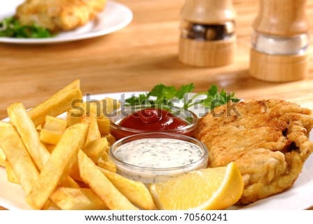 White plate with Fish and chips, mayo and ketchup