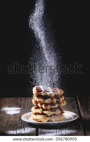 White plate with homemade belgian waffles with Sifting sugar powder over black background. sugar powder over old wooden table. Dark rustic style.
