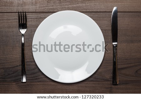 white plate with knife and fork on wooden table background