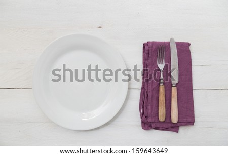 White plates and silverware on a light wood background