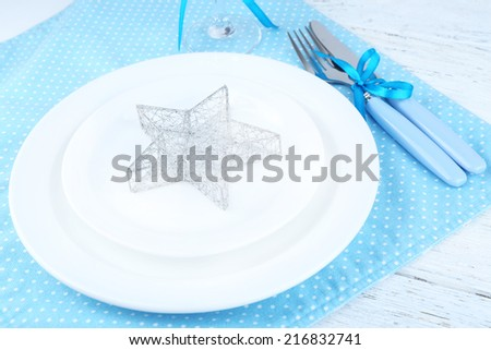 White plates, fork, knife and Christmas decoration on blue polka dot napkin on wooden background