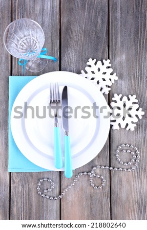 White plates, fork, knife, goblet and Christmas tree decoration on wooden background