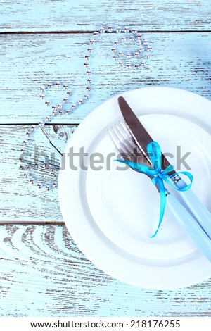 White plates, fork, knife, napkin and Christmas decoration on wooden background