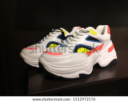 White platform sneakers with bright color accents on shelf in shoes store. Mass market shop. Close View Of Fashion Casual Female Sneakers. High Platform Sneakers For Women. Fashion Casual sneakers