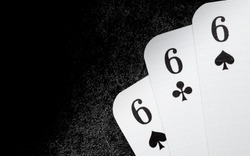 white playing cards 666 six of spades and six of clubs in the right lower corner on black cast iron surface with copy space at the left side, three of a kind, triple six