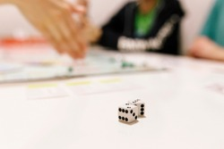 White Playing dice on a table with people in background playing boardgame