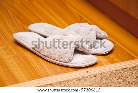 white plush slippers on hardwood floor. Concept - comfort and relaxation