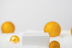 White podium of a geometric shape on the snow with golden balls. Winter festive scene for the presentation of cosmetics, product. Showcase with cube pedestal and minimalist Christmas decor