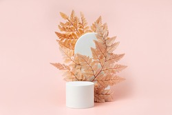 White podium with branch of leaves and arch to show cosmetic products. Beige color background for branding and packaging presentation.