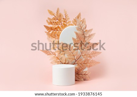 White podium with branch of leaves and arch to show cosmetic products. Beige color background for branding and packaging presentation. 商業照片 ©