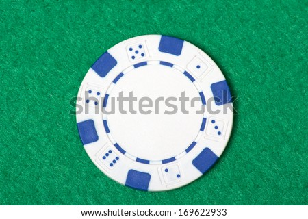 white poker chip on the green casino table