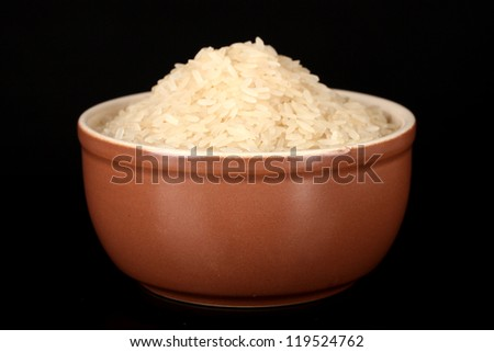 White polished rice in brown bowl isolated on black