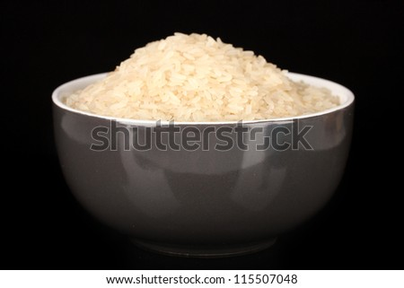 White polished rice in gray bowl isolated on black