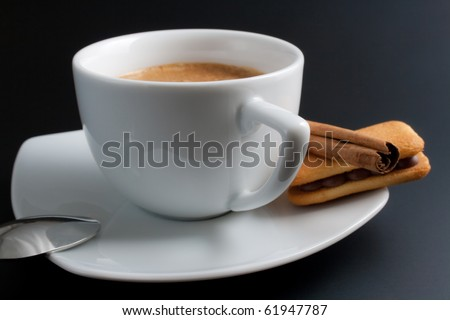 White porcelain cup of freshly brewed coffee arranged with plate, spoon, sandwich-biscuit and cinnamon stick isolated on dark background
