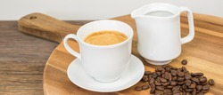 White porcelain cup of frothy coffee, jug of milk and fresh coffee beans on wooden serving tray.
