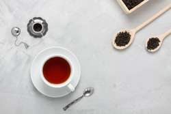 White porcelain cup of tea, small silver spoon, teapot used for brewing loose leaf tea  and wooden box spoons on grey concrete background. Food, beverage background.  Horizontal orientation, top view.