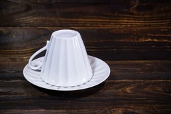 White porcelain cup turned upside down on saucer. On dark brown wooden surface.