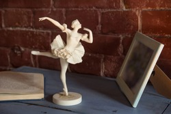 White porcelain figurine of a ballerina with an open book against a brick wall background