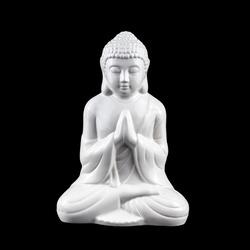 White, porcelain statuette of sitting meditating Buddha isolated on black