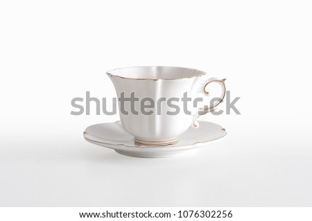 White porcelain tea cup with a golden line decoration and a saucer, on white background with clipping path, ready to cut out