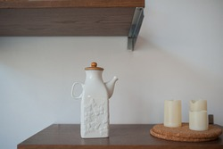 white porcelain teapot with butterfly pattern, electric candles on a wicker stand, on wooden shelves