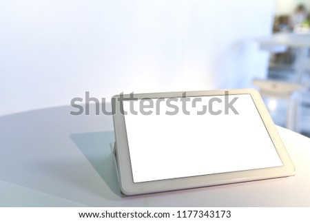 White portable smart tablet device and bright blank monitor screen place on the table in restaurant to order some items using for UX UI design application or business advertising e-commerce copy space #1177343173
