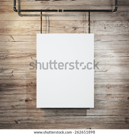 White poster hanging on leather belt on wood background